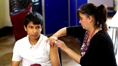 Pupil receiving vaccination from school nurse